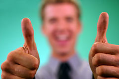 Business Thumbs UP. Two thumbs up in foregrounds, happy businessman's smiling face in blurred background on green Royalty Free Stock Photography