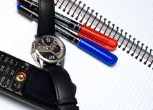 Business time. Two pens, watch, notebook, cellular phone Royalty Free Stock Photography