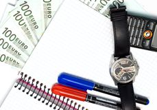 Business time. Euro bills, two pens, watch, notebook, cellular phone Stock Image