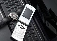 Business time. Cellular phone and watch on a laptop Royalty Free Stock Photo