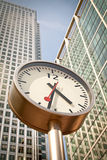Business time. Clock in Canary Wharf, outside Reuters. Focus on clock's face and arms Royalty Free Stock Image