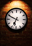 Business Time. Brick wall with light effect and clock Stock Images