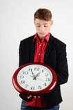 Business time. Business man holding and looking to a big clock. Stock Images