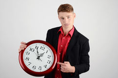 Business time. Business man holding and pointing to a big clock. Royalty Free Stock Photo