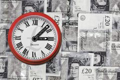 Business time clock. Clock with business time sign on the arrows on collage of twenty english pounds background Stock Images