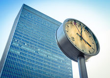 Business time. A contemporary skyscraper in the London Docklands business district with a clock in the foreground marking the time stock photo