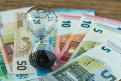 Business time countdown or long term investment concept as hourglass or sandglass on pile of Euro banknotes stock photography