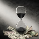 Business Time Money Hourglass. An hourglass resting on a pile of American money Stock Images