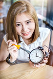 Business timing concept. Beautiful asian girl try to fixed black alarmclock on wooden table business timing concept stock photography
