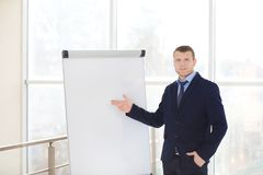 Business trainer giving presentation. On flip chart board indoors Royalty Free Stock Image
