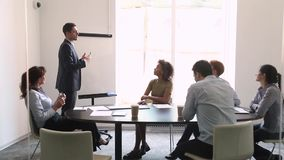 Business trainer makes presentation for corporate staff businesspeople gathered indoors. Experienced business trainer in suit make presentation use flip chart stock video footage