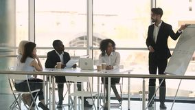 Diverse businesspeople sitting at table listening business coach during training. Business trainer standing in front of sitting diverse staff reporting about stock footage