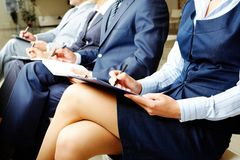 Business training. Photo of documents lying on business people�s legs at briefing stock photography