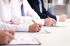 Business training. Business people participating in a seminar and taking notes royalty free stock photo