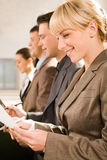 Business training. Row of four business people studing a document at seminar stock photography