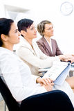 Business Training. Three businesswoman attending on business training. Sitting in a row, making notes, smiling Stock Image
