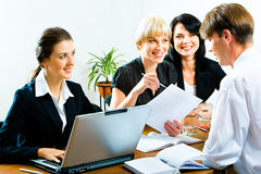 Business training. Three businesswomen looking at businessman with smiles during business seminar in the office with green plant on the background stock photography