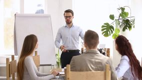 During business training all participants raise hands voting unanimously. Business coach stands in front of new employees talking provide developmental coaching stock video