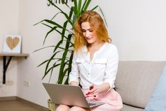 Business and training. beautiful young red haired long hair Caucasian woman uses laptop while sitting on sofa in room. She is dres stock photo