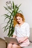 Business and training. beautiful young red haired long hair Caucasian woman uses laptop while sitting on sofa in room. She is dres stock photos