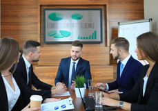 Business training. At office, business men presenting successful financial numbers on screen of plasma TV at meeting room Royalty Free Stock Photography