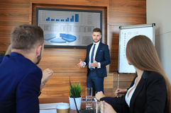Business training. At office, business men presenting successful financial numbers on screen of plasma TV at meeting room royalty free stock photos