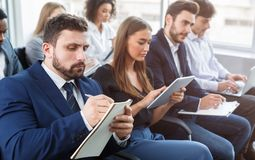 Business training, people making notes at seminar. Business training. Managers making notes at seminar, listening to speaker stock photo