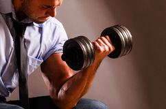 Business training. Strong business man is raising a dumbbell royalty free stock photo
