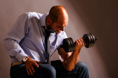 Business training. Strong business man is raising a dumbbell stock image