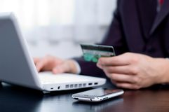 Business transaction. Businessman using his credit card for an online transaction Stock Photo