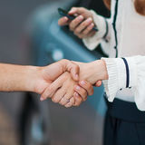 Business transaction. She shakes hands with a man buying a car Royalty Free Stock Photos