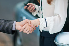 Business transaction. She shakes hands with a man buying a car Stock Photos