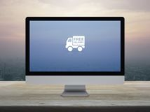 Business transportation online concept. Free delivery truck flat icon on desktop modern computer monitor screen on wooden table over city tower and skyscraper at stock images