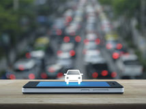Business transportation service concept. Car flat icon on modern smart phone screen on wooden table over blur of rush hour with cars and road, Business Stock Photography