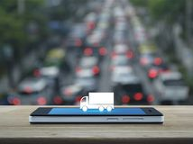 Business transportation service concept. Truck flat icon on modern smart phone screen on wooden table over blur of rush hour with cars and road, Business royalty free stock photo