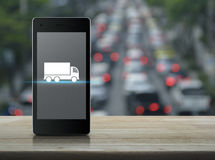 Business transportation service concept. Truck flat icon on modern smart phone screen on wooden table over blur of rush hour with cars and road, Business Stock Photo