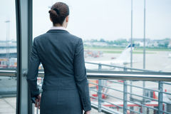 Business travel. Business woman standing at airport in front of landing runway stock photo