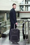 Business Travel. Young businessman with a suitcase and plane tickets at the airport to travel trips Royalty Free Stock Photo