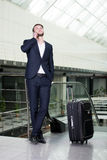 Business Travel. Young businessman with a suitcase and plane tickets at the airport to travel trips Stock Photography