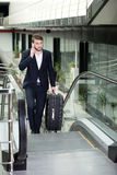 Business Travel. Young businessman with a suitcase and plane tickets at the airport to travel trips Royalty Free Stock Image