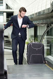 Business Travel. Young businessman with a suitcase and plane tickets at the airport to travel trips Royalty Free Stock Images