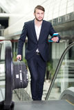 Business Travel. Young businessman with a suitcase and plane tickets at the airport to travel trips Stock Image