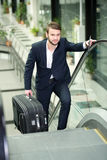 Business Travel. Young businessman with a suitcase and plane tickets at the airport to travel trips Stock Photos