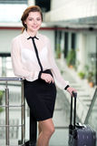 Business Travel. Young business woman with suitcase and plane tickets at the airport to travel trips Stock Photos