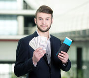 Business Travel. Young businessman with a suitcase and plane tickets at the airport to travel trips Royalty Free Stock Photography