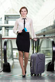 Business Travel. Young business woman with suitcase and plane tickets at the airport to travel trips Royalty Free Stock Photos