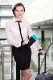 Business Travel. Young business woman with suitcase and plane tickets at the airport to travel trips Stock Photography