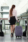 Business Travel. Young business woman with suitcase and plane tickets at the airport to travel trips Royalty Free Stock Photo
