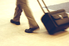 Business Travel. Fast walking business man (blurred legs and luggage only) pulling a small suitcase on wheels Royalty Free Stock Photography