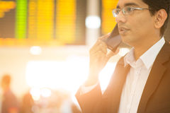 Business travel. Asian Indian Business man on the phone during his business travel, at the airport, golden sun light background Stock Image